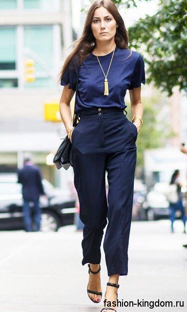 Золотые украшения и небольшая сумочка в сочетании с классическими темно-синими брюками и блузкой с короткими рукавами.