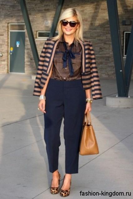 Классические брюки черного цвета сочетаются с блузкой медного тона и жакетом черно-коричневой расцветки в полоску.