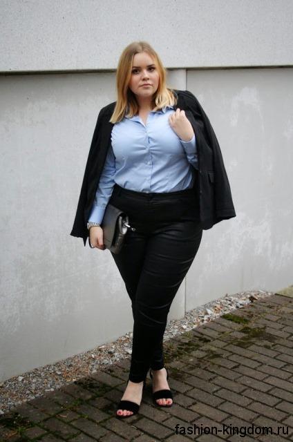 Черные брюки зауженного фасона сочетаются с голубой рубашкой и классическим пиджаком черного цвета.