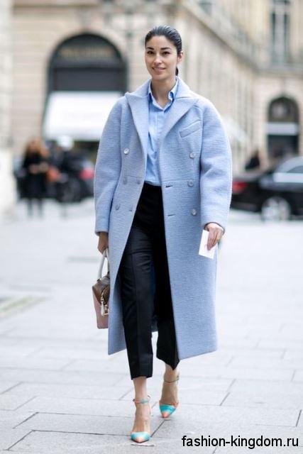 Осеннее пальто прямого фасона, голубого цвета, длиной ниже колен сочетается с классическими черными брюками.