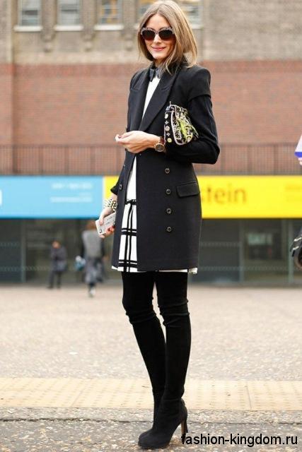 Классическое осеннее пальто черного цвета, приталенного фасона в тандеме с черно-белой юбкой и высокими сапогами.