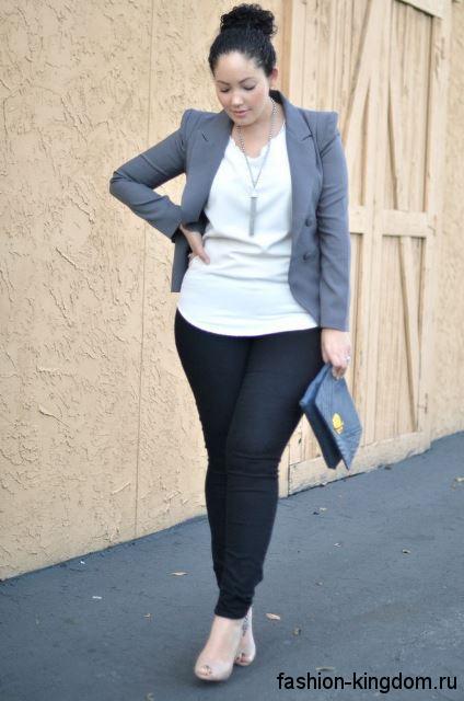 Узкие черные джинсы в сочетании с блузой белого цвета и пиджаком серого тона классического фасона.