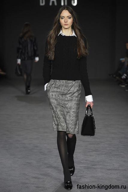 Классическая серая юбка-карандаш в клетку, длиной до колен в сочетании с черной кофточкой и туфлями на каблуке от Daks.