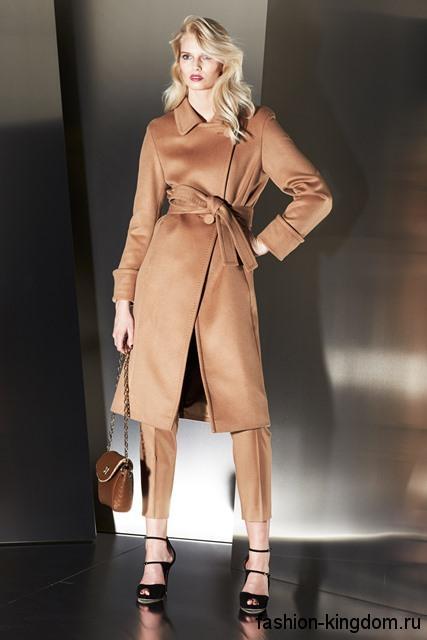 Укороченные брюки бежевого цвета, классического покроя сочетаются с демисезонным бежевым пальто длиной до колен от Escada.