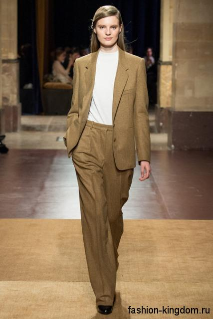 Классический брючный костюм светло-коричневого цвета в сочетании с белой блузкой и туфлями на каблуке от Hermes.