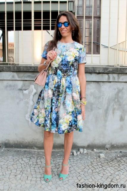 Платье в стиле ретро голубого тона с цветочным принтом, длиной до колен, с короткими рукавами.